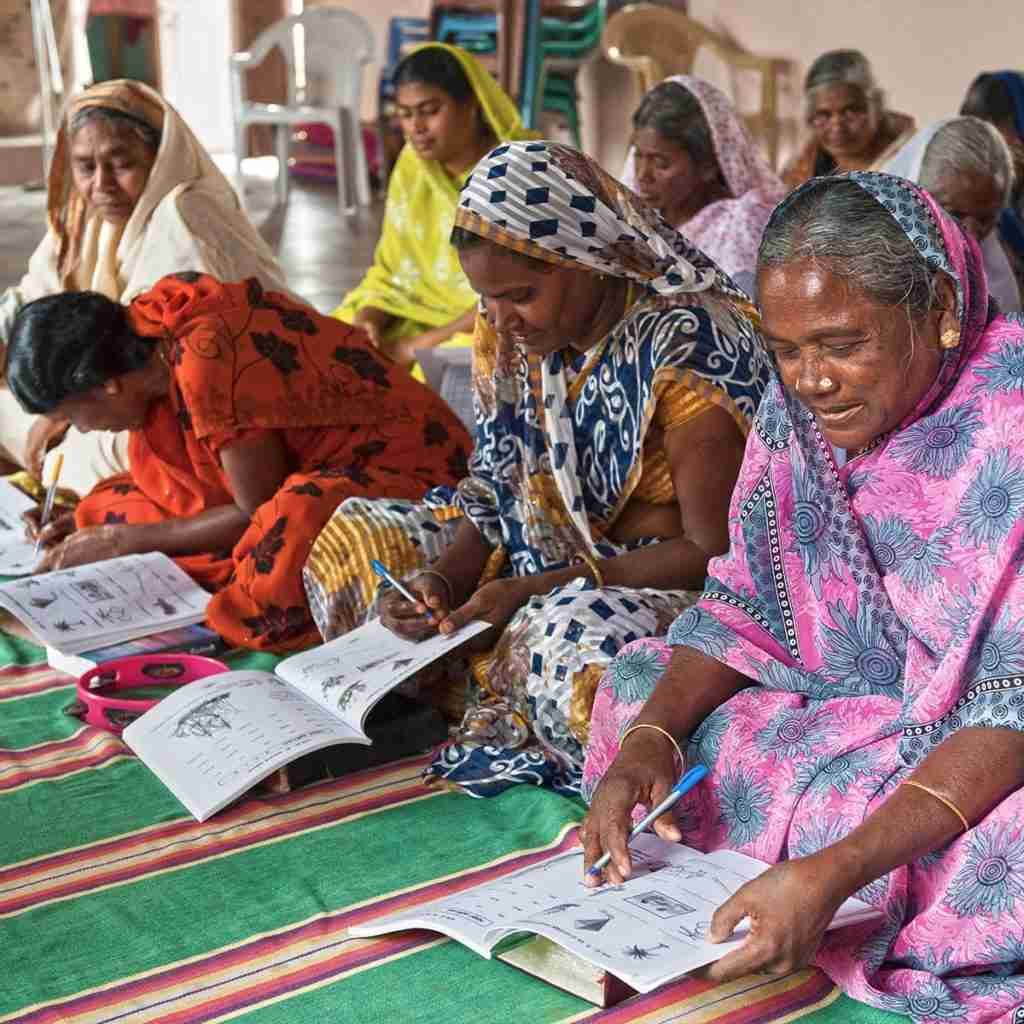 Adult women learning how to read and write in GFA World Literacy Class