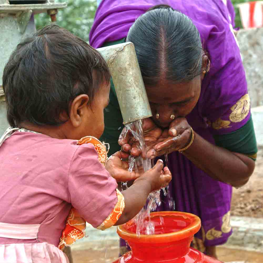 Woman and little girl drinking clean water from GFA World Jesus Wells